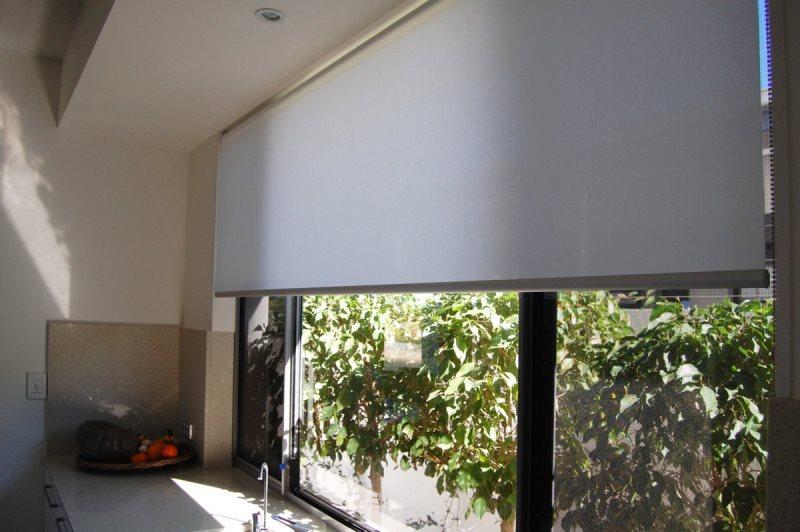 широкая рулонная штора на окне в кухне