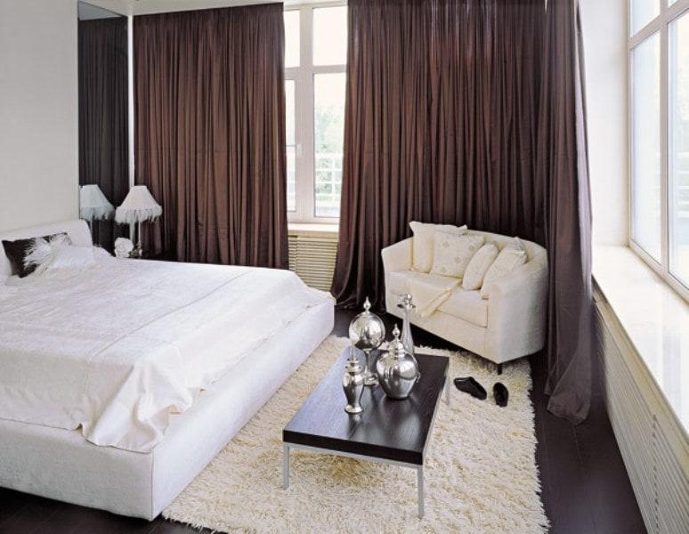 белая кровать на фоне коричневых портьер