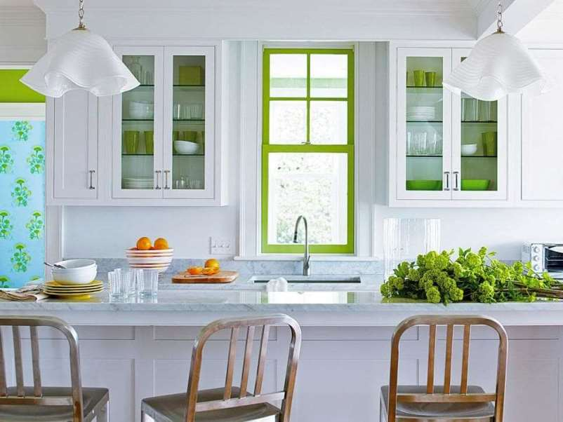 зеленая рама на окне придает изюминку в белой кухне