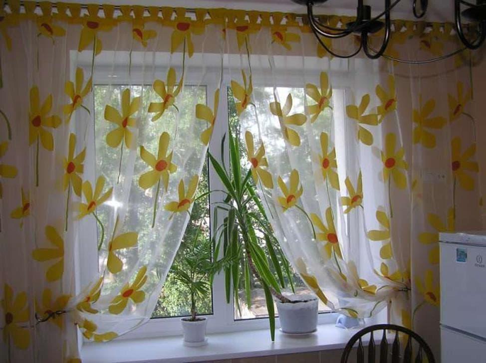окно кухни с прозрачными занавесками на которых присутствует цветочный узор