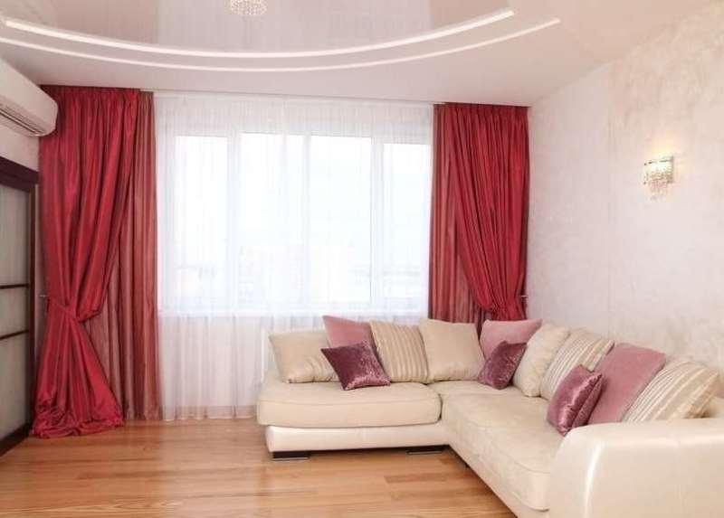 красные и розовые шторы на окнах и мебель молочного цвета