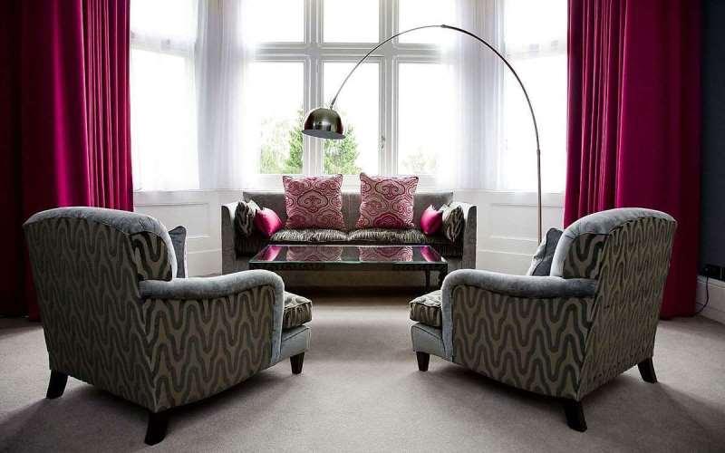 шторы цвета фуксия в гостиной с эркерным окном