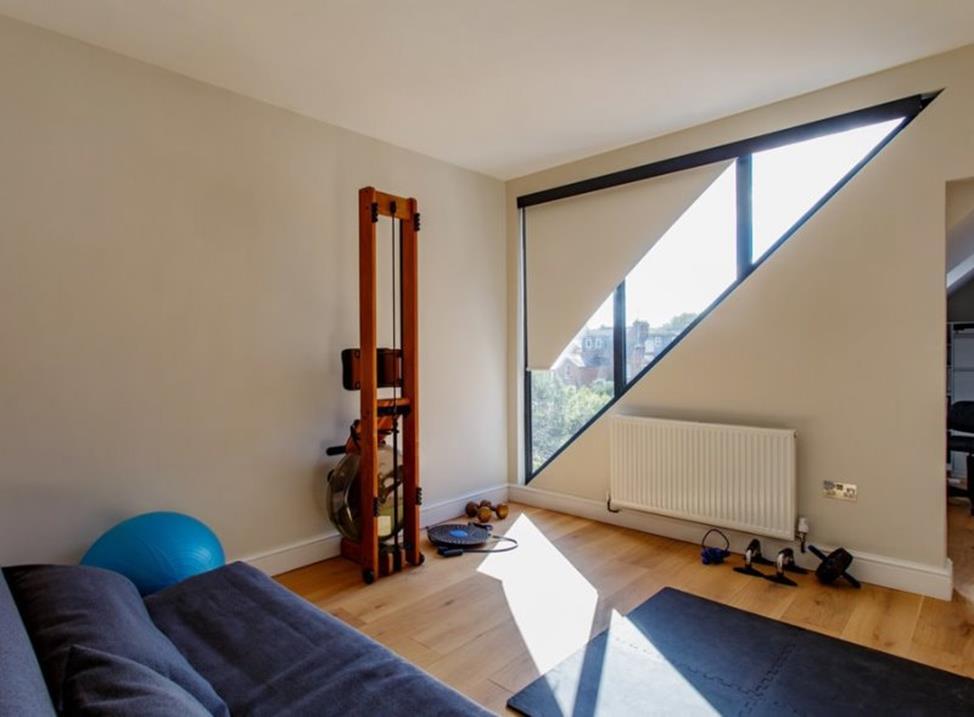 квартира с треугольным окном и рулонными шторами на нем