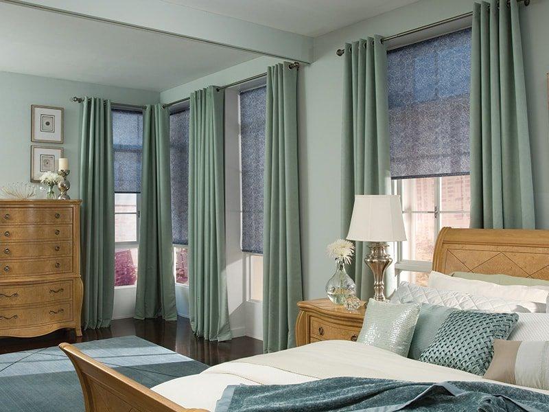 сочетание портьер с люверсами и рулонок в спальне с панорамными окнами