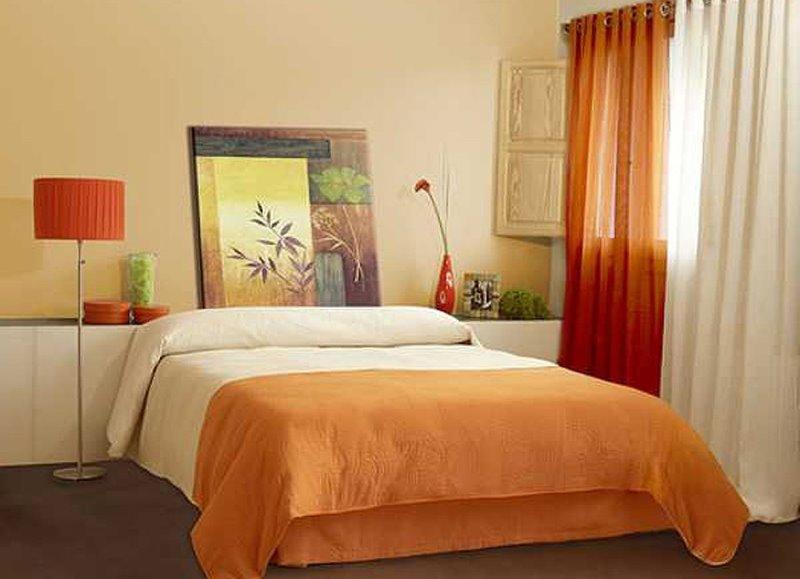сочетание штор терракотового цвета и постельного покрывала