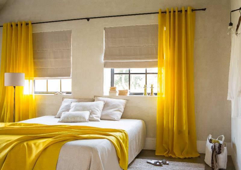 сочетание солнечных портьер с римскими шторами в спальне